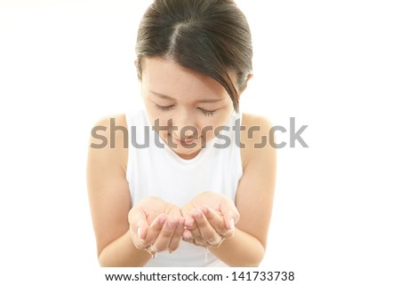 Beautiful young woman wash her face with water