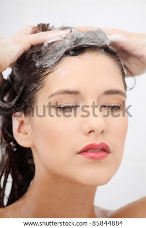 Beautiful young woman washing her hairs in a shower