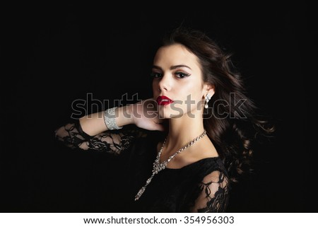 Beautiful young woman wearing a classic black lace dress and crystal jewelery with wind blown hair.  Shot on black background.