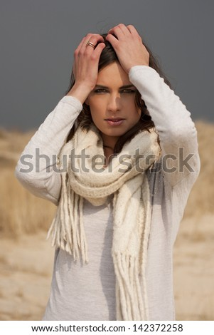 Beautiful young woman wearing a grey shirt and a white scarf posing in the dunes