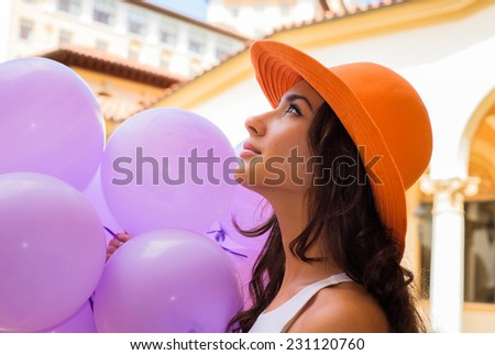 Beautiful young woman wearing a hat and holding balloons in a outdoor courtyard setting. - stock photo