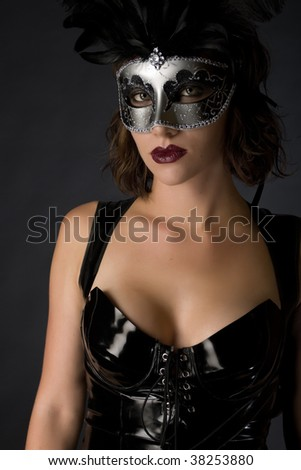 Beautiful young woman wearing a latex catsuit and mask - stock photo