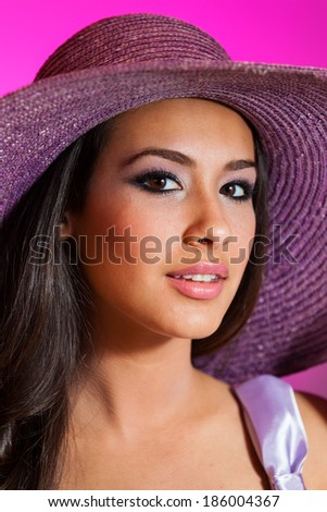 Beautiful young woman wearing a purple hat on a purple background.