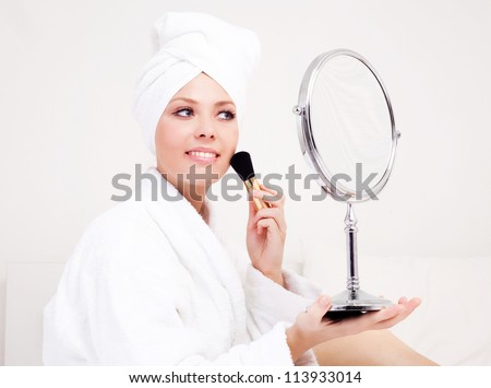beautiful young woman wearing a towel and a white bathrobe and holding a brush and mirror, isolated against white background - stock photo