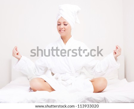 beautiful young woman wearing a towel and a white bathrobe meditating in  the bed at home - stock photo