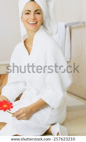 beautiful young woman wearing a towel and a white bathrobe on the bed at home - stock photo