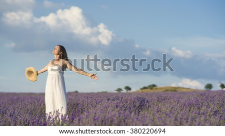 Beautiful young woman wearing a white dress celebrating the beauty of life standing in the middle of a lavender field in bloom. - stock photo