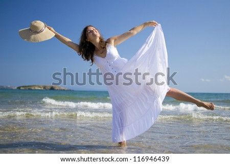 Beautiful young woman wearing a white dress having fun in the sea