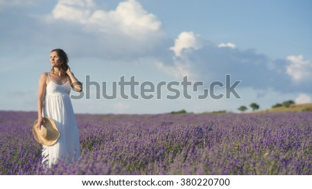 Beautiful young woman wearing a white dress standing in a middle of a lavender field in bloom. - stock photo