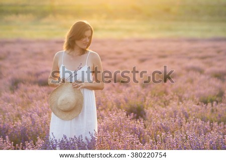 Beautiful young woman wearing a white dress standing in a moment of peace and serenity  in a middle of a lavender field under the golden light of sunset. - stock photo