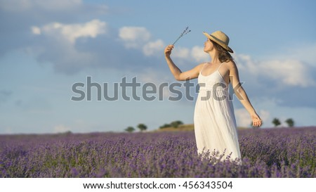 Beautiful young woman wearing a white dress standing in the middle of a lavender field holding a few blades of  lavender. - stock photo