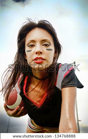Beautiful young woman wearing American Football attire holding ball ready for action - stock photo