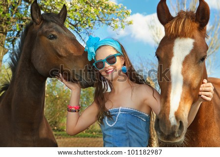 Beautiful young woman wearing blue dress with a horses outdoor.