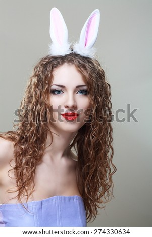 beautiful young woman wearing cute bunny ears looking to her side