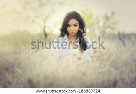 Beautiful young woman wearing denim top and short bottoms in ethereal Arizona dry desert landscape. - stock photo
