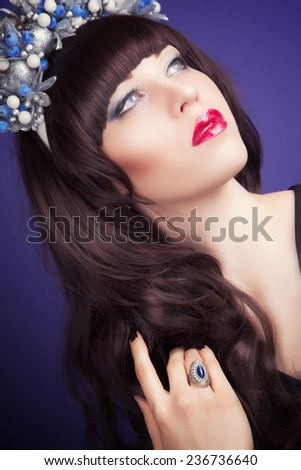 beautiful young woman wearing designer wreath and posing against blue background