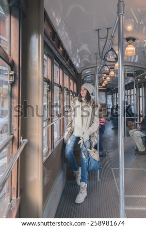 Beautiful young woman wearing ecological fur poses on a tram