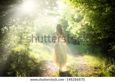 Beautiful young woman wearing elegant white dress standing with a smile on a road in the forest with rays of sunlight beaming through the leaves of the trees - stock photo