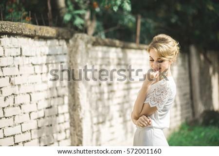 phụ nữ trẻ xinh đẹp mặc thanh lịch đầm trắng đứng với một nụ cười trên một con đường gần một bức tường trong rừng với các tia của ánh sáng mặt trời rạng rỡ thông qua các lá của cây