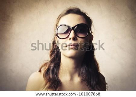 Beautiful young woman wearing fashion sunglasses - stock photo