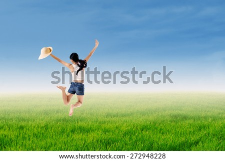 Beautiful young woman wearing hat jumping in the grass