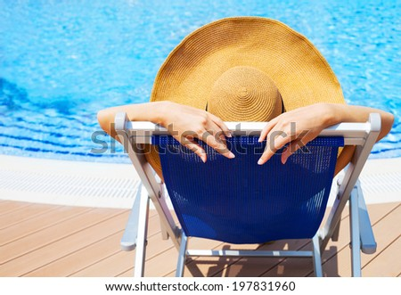 Beautiful young woman wearing hat lying on deckchair by swimming pool - stock photo