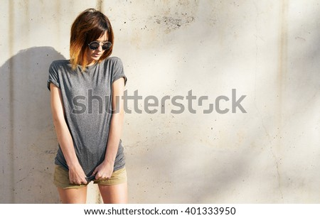 beautiful young woman wearing in a gray blank t-shirt posing against a background of a concrete wall in the rays of the setting sun - stock photo