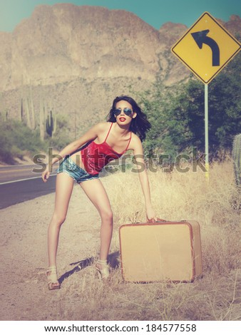 Beautiful young woman wearing little denim short beans and red bandana top with retro vintage suitcase standing on lonely desert mountain road - stock photo