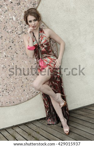 Beautiful young woman wearing luxury resort dress posing sexy against stone wall background.