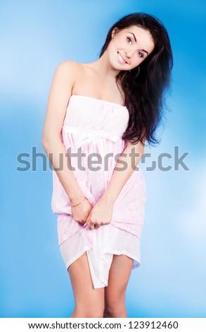 beautiful young woman wearing pajamas, on blue studio background - stock photo