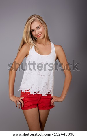 beautiful young woman wearing red shorts and white lace fashion top smiling on gray studio background - stock photo