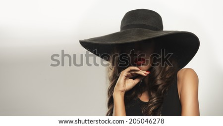 Beautiful young woman wearing summer black hat with large brim  - stock photo