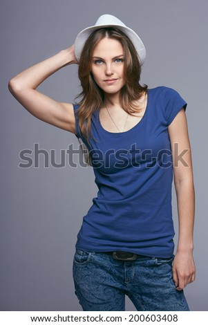 Beautiful young woman wearing summer fedora straw hat posing in studio against gray background - stock photo