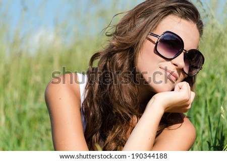 Beautiful young woman wearing sun glasses on summer day green outdoors background portrait  - stock photo