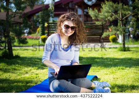 Beautiful young woman wearing sunglasses lying on the grass and working with a laptop