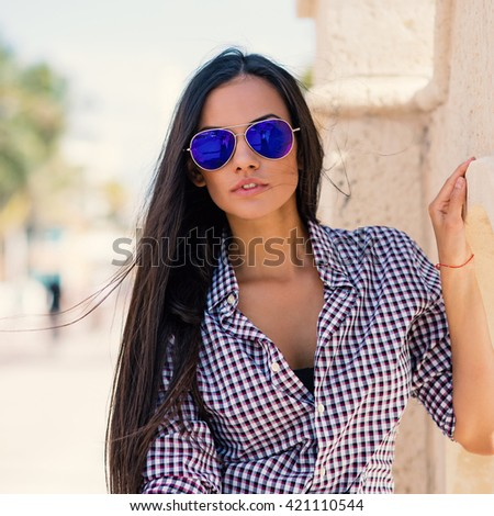 Beautiful young woman wearing sunglasses on the beach close up portrait. Filtered image.
