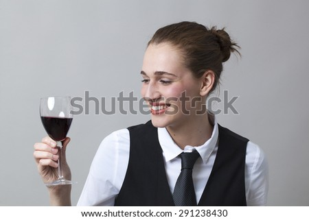 Beautiful young woman wearing uniform of wine waitress looking at aspect and color of red wine - stock photo