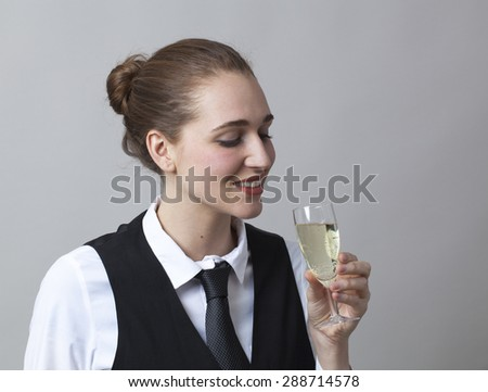 Beautiful young woman wearing uniform of wine waitress tasting a bubbly wine in glass of Champagne - stock photo
