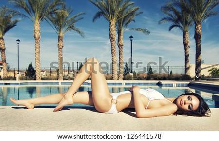 Beautiful young woman wearing white bikini swimsuit beside swimming pool. - stock photo
