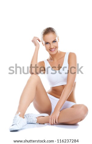 Beautiful young woman wearing white underwear sitting and smiling - stock photo