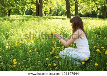 Beautiful young woman weaves a wreath of dandelions