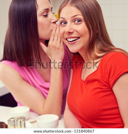 beautiful young woman whispering message to her friend