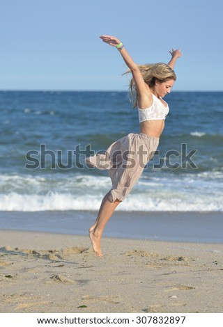 Beautiful young woman white lace top and flowing skirt dances on beach