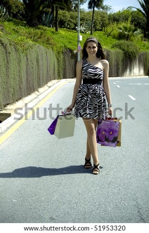 beautiful young woman who walks her shopping bags on the road