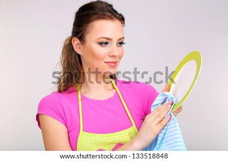 Beautiful young woman wipes clean plate in kitchen on grey background