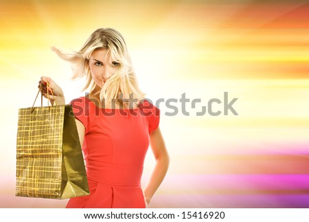 Beautiful young woman with a bag over abstract yellow background - stock photo