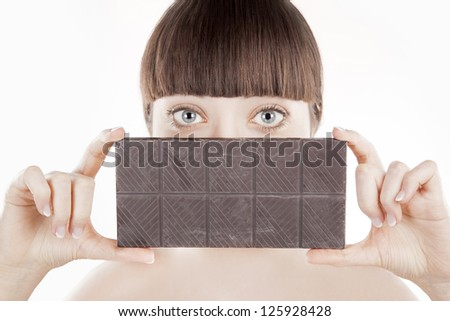 Beautiful young woman with a big chocolate bar (Series) - stock photo