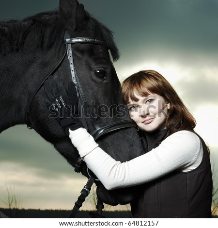 Beautiful young woman with a black horse - stock photo