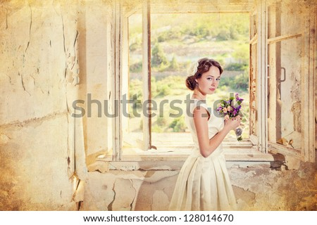 beautiful young woman with a bouquet of flowers is in the old room at the open window, photo of a woman with flowers in retro style - stock photo