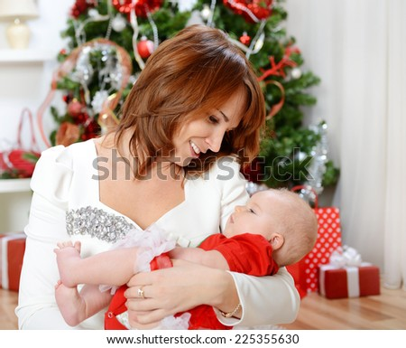 beautiful young woman with a child, baby girl ,in a Christmas interior with a Christmas tree. - stock photo